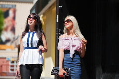 Two young fashion women walking on a street Royalty Free Stock Image