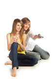 Young women watch TV. Two smiling pretty blond girls watch TV; isolated on white background Stock Image