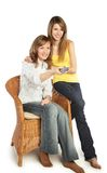 Young women watch TV. Two smiling pretty blond girls watch TV; isolated on white background Royalty Free Stock Image