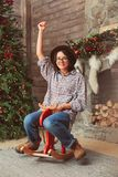 Laughing woman on wooden rocking horse stock photography