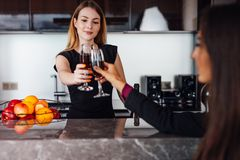 Young women wearing elegant black dress holding a bottle of red wine and a glass standing at kitchen bar looking at her. Female friend Royalty Free Stock Photography