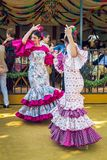 Young women wearing flamenco dresses and dancing `Sevillanas` at the April Fair, Seville Fair Feria de Sevilla. Sevilla, Spain - April 18, 2018: Young women stock image