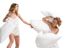 Girls hitting each other with pillows for fun royalty free stock image