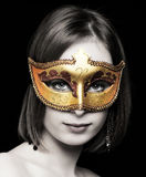 Young women wearing a mask. Young women wearing a red and gold  mask with selective desaturation Royalty Free Stock Photos