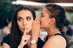 Gossiping Girl Telling Secrets to her Surprised Friend. Young women whispering something confidential to a schoolmate Stock Photos