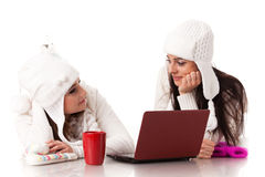 Young  women in winter clothes with laptop Stock Images