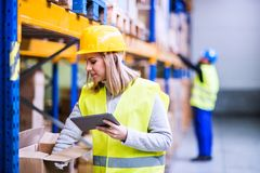 Woman warehouse worker with tablet. Young women worker or supervisor with tablet. Warehouse workers controlling stock royalty free stock photo