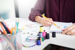 Young women working as fashion designer drawing sketches for clothes in atelier paper at workplace studio. Young women working as fashion designer drawing royalty free stock image