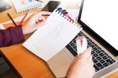Young women working as fashion designer drawing sketches for clothes in atelier paper at workplace studio. Young women working as fashion designer drawing royalty free stock photo