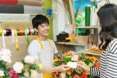 Young woman working as florist giving credit card to customer. Young women working as florist giving credit card to customer Stock Images