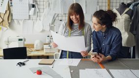Young women working in design industry are comparing sketches and talking about them while working in modern tailor shop. Attractive young women working in stock footage