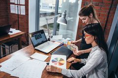 Young women working on a new web design using color swatches and sketches sitting at desk in modern office.  Stock Photography