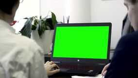 Young women working in office, sitting in chairs in front of computer with green screen, rear view. Two girls co workers