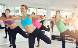 Young women working out in aerobics class. Young women in colorful sportswear working out in aerobics class at the gym with focus to a smiling slender lady in Royalty Free Stock Photo