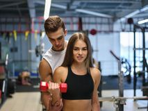 A woman doing exercises with dumbbells on a gym background. A personal trainer helping a client on a fitness club. A young women is working out bicep curls with Stock Photo