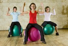 Young women working out siting on big balls Royalty Free Stock Photography