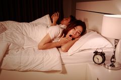 Woman yawning in bed while her husband using mobile phone next t. Young women yawning in bed while her husband using mobile phone next to her at night Royalty Free Stock Photography