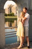 Young family couple hugging and watching the sun sunset. Young women in yellow dress and men in the park  hugging and watching the sun sunset Stock Image
