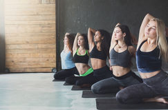 Young women in yoga class, mermaid pose stretching stock photography
