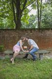 Couple kissing over cake celebrating one year anniversary. A young women and young men sitting on a bench kissing over a cake with one candle celebrating royalty free stock photo