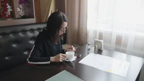 Young wonam use mobile phone while sitting in comfortable coffee shop during work break, charming happy female reading stock video footage