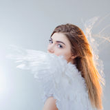 Young, wonderful blonde girl in the image of an angel with white wings. Stock Images