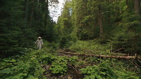 Young woodcutter in traditional ukrainian clothes with axe in the green forest stock video