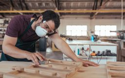 Young woodworker skillfully sanding furniture alone in his workshop Royalty Free Stock Photos