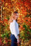 Young wooman. Dreamy pretty girl in bright autumn orange leaves. Young wooman. Dreamy pretty caucasian girl in bright autumn orange leaves. Vertical shoot royalty free stock image