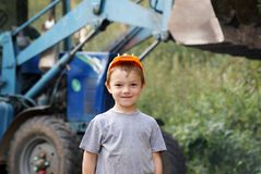 Young worker. Young boy in hard hat standing in front of  blue tractor Royalty Free Stock Photos