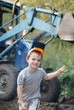 Young worker. A little boy is running away from big blue tractor Stock Image