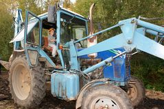 Young worker. Young boy pretending to drive a big tractor Stock Photography