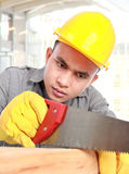 Young worker. Sawing wood in the building Royalty Free Stock Image