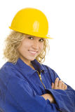 Young worker. Young female worker in a blue jumpsuit and a yellow hardhat stock photography