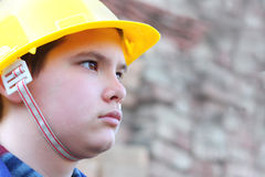 Young worker against the blurred brick wall Royalty Free Stock Photo