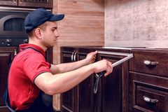 A young worker is assembling modern wooden kitchen furniture royalty free stock images