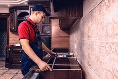 .A young worker is assembling modern wooden kitchen furniture stock images