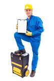 Young worker with a blank clipboard supporting his foot on his Royalty Free Stock Photos