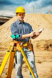 A young worker with clipboard on construction site.  Royalty Free Stock Images
