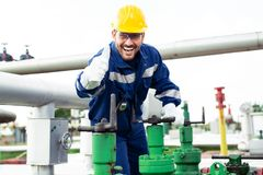 Worker closes the valve on the oil pipeline royalty free stock photography