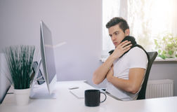 Young worker with a cold. Freelancer in scarf and cup of tea in the office. Designer the sick throat in the stock image