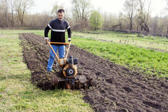 Young worker cultivates the soil. Young farmer plows a field in spring with motocultivator Royalty Free Stock Image