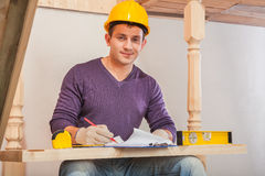 Young worker drawing with pencil in blueprint Royalty Free Stock Image
