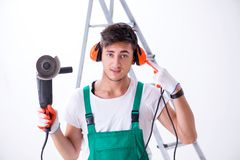 The young worker with earmuffs in noise cancelling concept. Young worker with earmuffs in noise cancelling concept stock photography