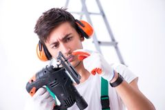 The young worker with earmuffs in noise cancelling concept. Young worker with earmuffs in noise cancelling concept royalty free stock photography