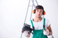 The young worker with earmuffs in noise cancelling concept. Young worker with earmuffs in noise cancelling concept stock image