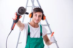 The young worker with earmuffs in noise cancelling concept. Young worker with earmuffs in noise cancelling concept royalty free stock photo