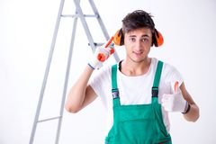 The young worker with earmuffs in noise cancelling concept. Young worker with earmuffs in noise cancelling concept stock photos