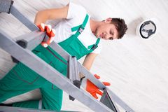The young worker falling from the ladder royalty free stock image