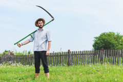 Young worker in the field. Worker with a reaper in the field Royalty Free Stock Photography